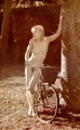 Nude Madonna posing by the old fashioned bicycle