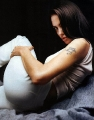 Angelina Jolie laying, showing tatoo